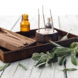 Sage leaves and wooden box with aromatherapy oils and incense sticks on wooden background