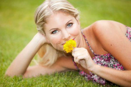 Woman on grass with flower