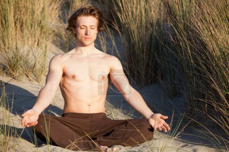 Photo for Young man doing yoga on sand dunes - Royalty Free Image