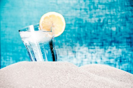 Photo for A drink with ice and lemon on the beach in the summer on blue background - Royalty Free Image