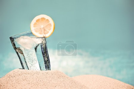 Photo for Cold drink with ice and a slice of lemon on the beach on a hot summer day - Royalty Free Image