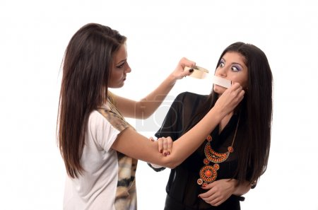 Girl taping her friends mouth shut with duct tape