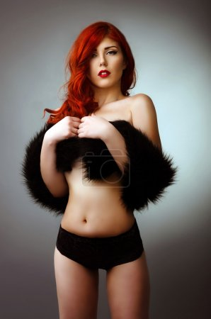 Sexy topless woman covering her chest with a black fur coat