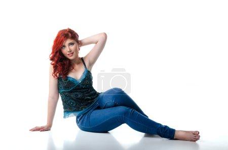 Young barefoot woman sitting on the studio floor