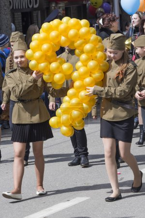 Two girls at the parade with balloons in form of digit nine (the
