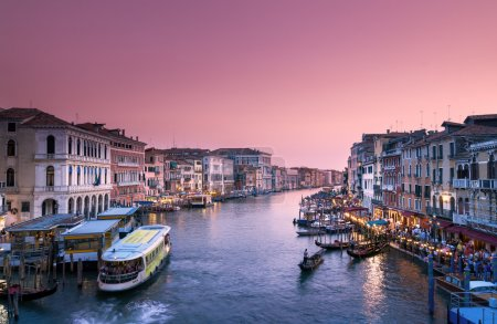 Photo for Famous Grand canal of Venice at dusk. People going about there business in gondolas and vaporati (taxi boat). - Royalty Free Image