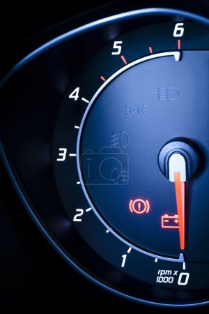 Fragment of instrument panel of car speedometer, tachometer with visible symbols of instrument cluster.