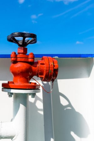Red water or fuel valve against blue sky background.