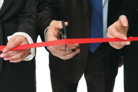 Photo pour Gens d'affaires coupant un ruban rouge avec une paire de ciseaux, closeup - image libre de droit