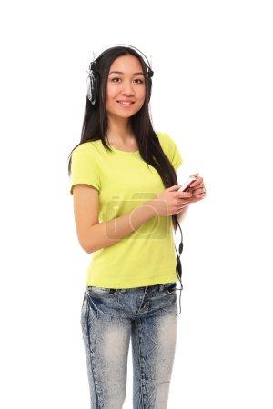 Foto de Una chica asiática universitaria en auriculares con teléfono móvil - Imagen libre de derechos