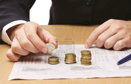 Photo pour Homme d'affaires mettre les pièces en colonnes - image libre de droit