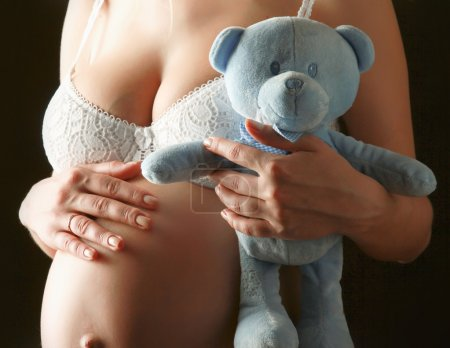 Pregnant woman holding a toy