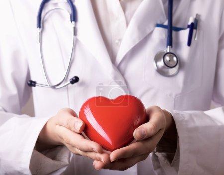 Photo pour Médecin femme avec stéthoscope tenant le cœur, isolé sur fond blanc - image libre de droit