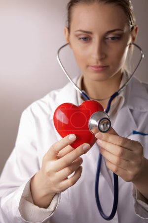 Doctor with stethoscope examining red heart
