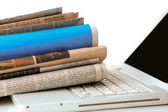 stack of newspaper next to a laptop.