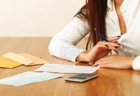 Young woman using a calculator.