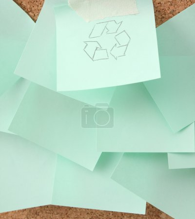 Recycle sign on green sheet of paper.
