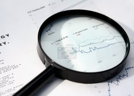 magnifying glass over financial newspaper.