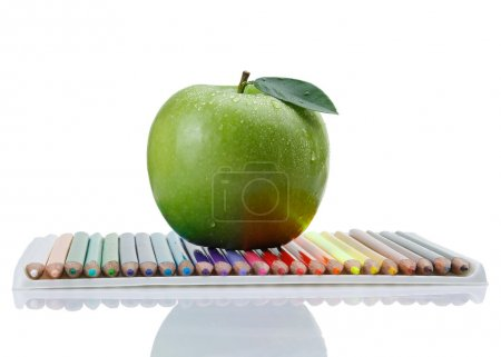 Colored pencils and  green apple