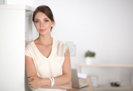 Close-up portrait of a smiling  business woman standing in her office