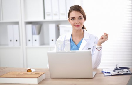 Female doctor sitting on the desk and working a la...