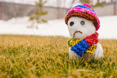 Sad snowman with hat and scarf