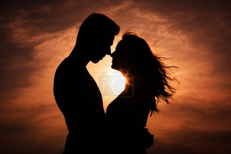 Couple in love silhouette during sunset - touching...