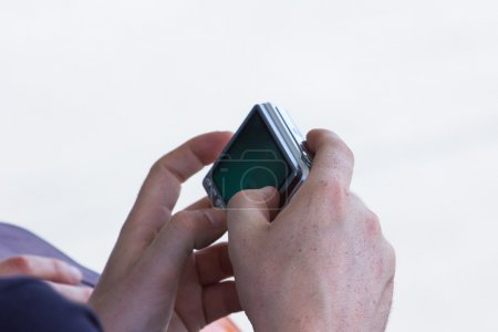 Closeup image of two hands holding black compact digital photo c