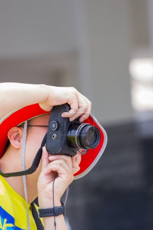 man with red hat taking a photo with black camera