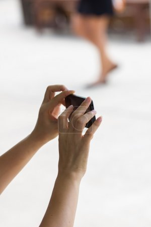 Hands of female taking a picture with mobile phone