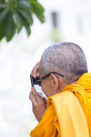 Monk taking a picture with mobile phone in Thailand