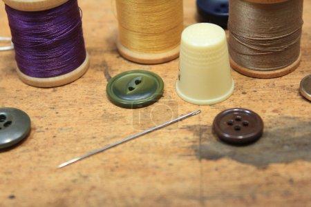 Photo pour Notions de couture, boutons aiguille et fil sur fond bois rustique - image libre de droit