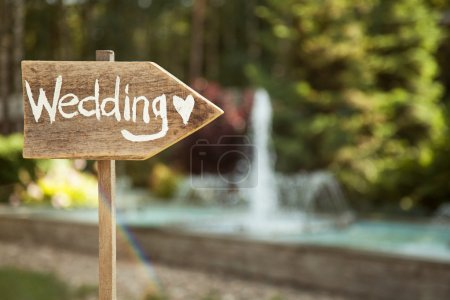 Wedding decor. Wooden plaque with the inscription Wedding. Wedding on a plate green background and a fountain. Wedding decorations are beautiful. Summer wedding celebration.