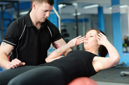 Photo for Personal trainer helping young woman in gym - Royalty Free Image