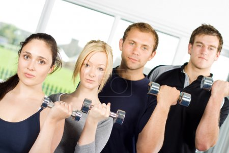 Photo for Group of young people lifting weights in the gym - Royalty Free Image