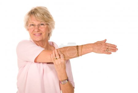 Photo for Mature older lady performing stretching exercises before gym workout - Royalty Free Image