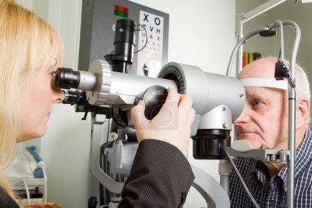 Photo pour Un homme plus âgé passe un examen oculaire dans une clinique d'opticiens - image libre de droit