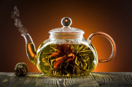 Glass teapot with blooming tea flower on wooden table