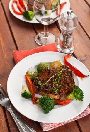 Grilled pork chops with vegetables on the table...