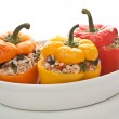 Stuffed peppers in a dish on white background...