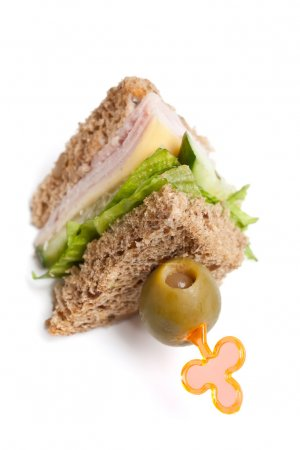 Photo for Club tea sandwich with ham, cheese, lettuce and cucumbers on whole wheat bread - Royalty Free Image