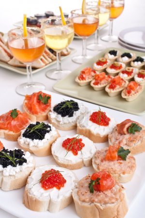 Photo for Big banquet table with cocktails, small sandwiches and canapes - Royalty Free Image