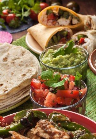 Photo for Traditional mexican food: cilantro and lime rice, chicken fajitas, fajita peppers, burritos, tortillas, guacamole and salsa - Royalty Free Image