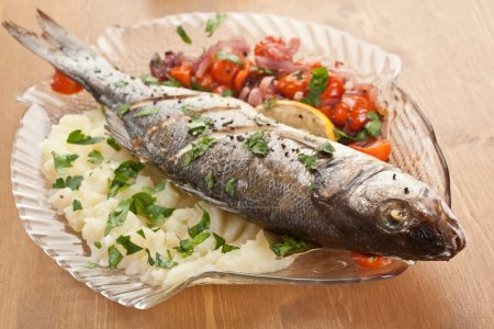 Photo for Seabas fish baked with vegetables, herbs and lemon on a dish - Royalty Free Image