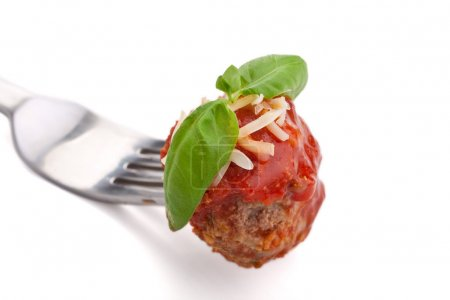 Photo for Meatball with tomato sauce, grated cheese and basil on a fork - Royalty Free Image
