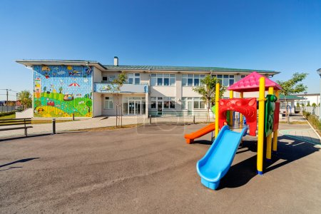 Photo for Preschool building exterior with playground on a sunny day - Royalty Free Image
