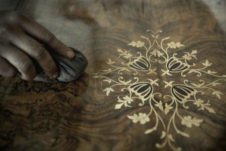 African Carpenter Polishing Antiques