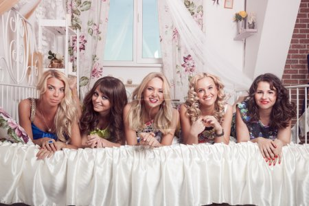 Group of cheerful beautiful woman lying on bed. Bachelorette.