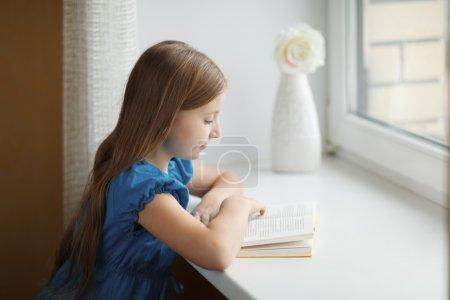 Little girl reading book on windowsill