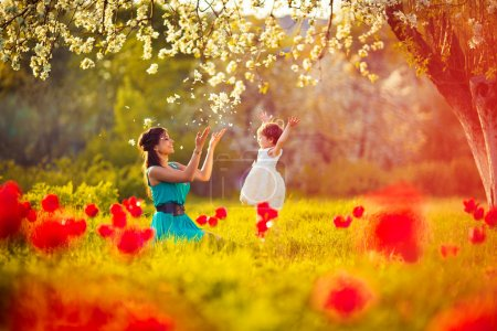 Photo for Happy woman and child in the blooming spring garden.Mothers day holiday concept - Royalty Free Image